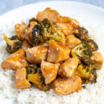 Pinterest Pin for Baked General Tso's Chicken showing a plate full of steamed rice topped with saucy chicken and broccoli