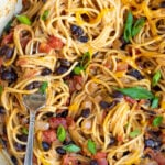 Pinterest Pin for One-Pot Taco Spaghetti with image of close up of cooked spaghetti with black beans, tomatoes, and cheese
