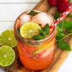 Pinterest Pin for Strawberry Mojito Mocktail showing a pink beverage in a glass with ice garnished with fresh mint and lime slices