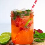 Pinterest Pin for Strawberry Mojito Mocktail showing an image of a glass filled with pink mocktail garnished with fresh mint and lime slices