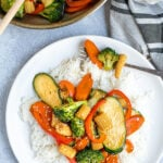 Pinterest Pin for Easy Veggie Stir Fry with a photo of vegetables on a bed of white rice with a forkful of veggies