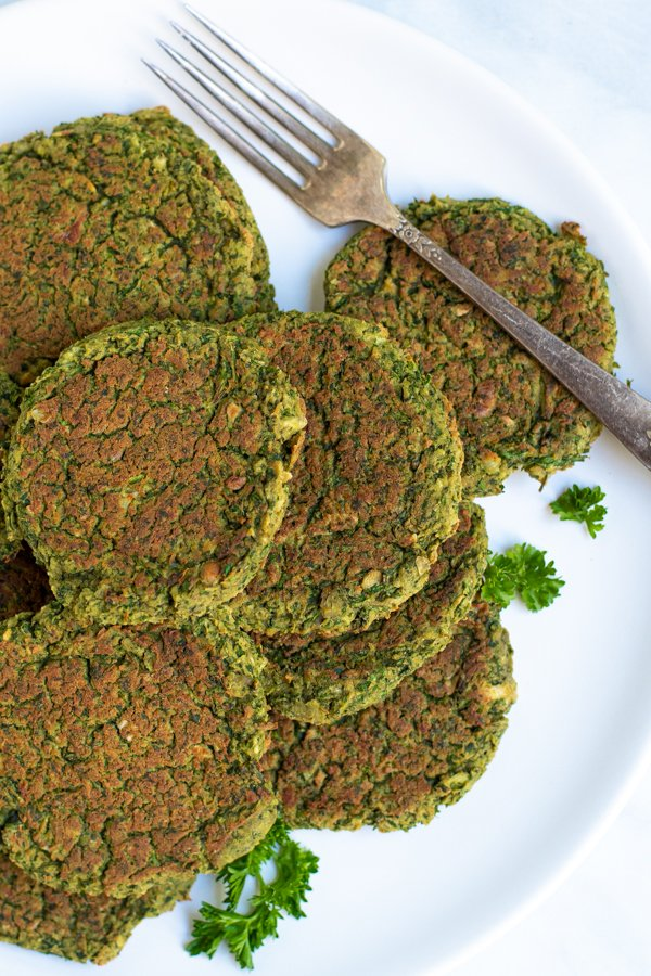 oven baked falafel piled on a white plate next to parsley and a fork