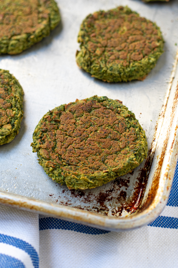 close up a a patty of baked falafel on a sheet pan