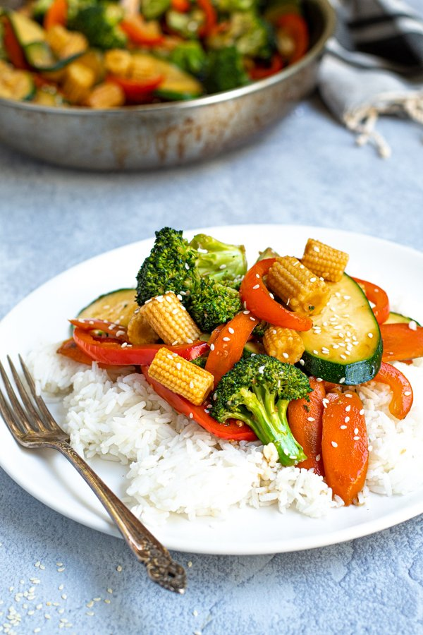easy vegetables stir fry on a plate served with rice and garnished with sesame seeds