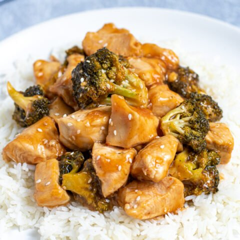 close up view of baked General Tso's Chicken on a bed of rice on a white plate