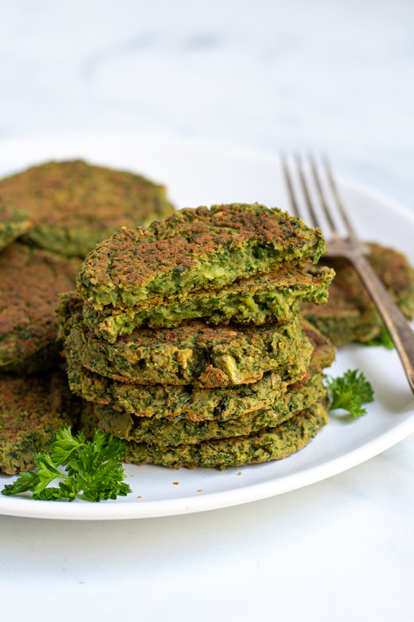 Stack of healthy oven baked falafel on a plate with the top falafel broken open to reveal a green inside
