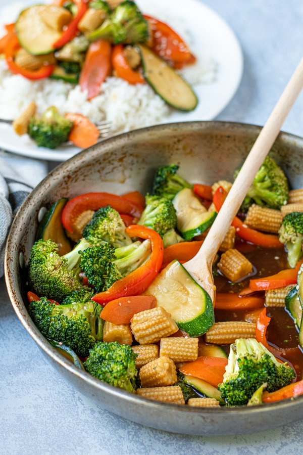 simple vegetable stir fry in a skillet with a wooden spoon