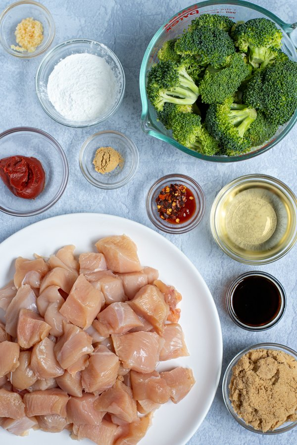 all of the ingredients needed to make healthy baked general tso chicken laid out including diced chicken and broccoli