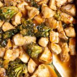 Pinterest Pin for Baked General Tso's Chicken showing the saucy chicle and broccoli up close in the baking dish