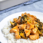 Pinterest Pin for Baked General Tso's Chicken showing a plate with rice topped with a large scoop of saucy chicken and broccoli