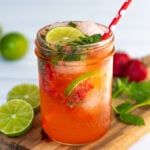 Pinterest Pin for Strawberry Mojito Mocktail showing a photo of a glass of pink beverage garnished with limes and fresh mint