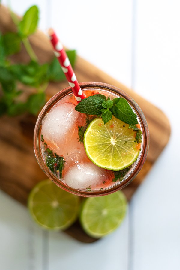 an overhead view of a glass of strawberry mojito mocktail showing lime slices and fresh mint as garnishes
