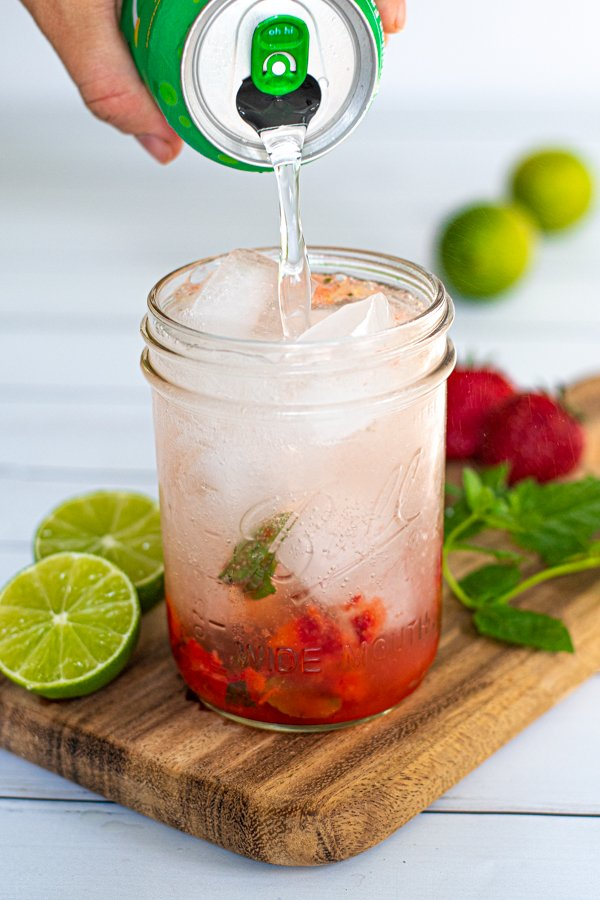 a lime seltzer being poured into a glass full of ice and muddled strawberries and mint