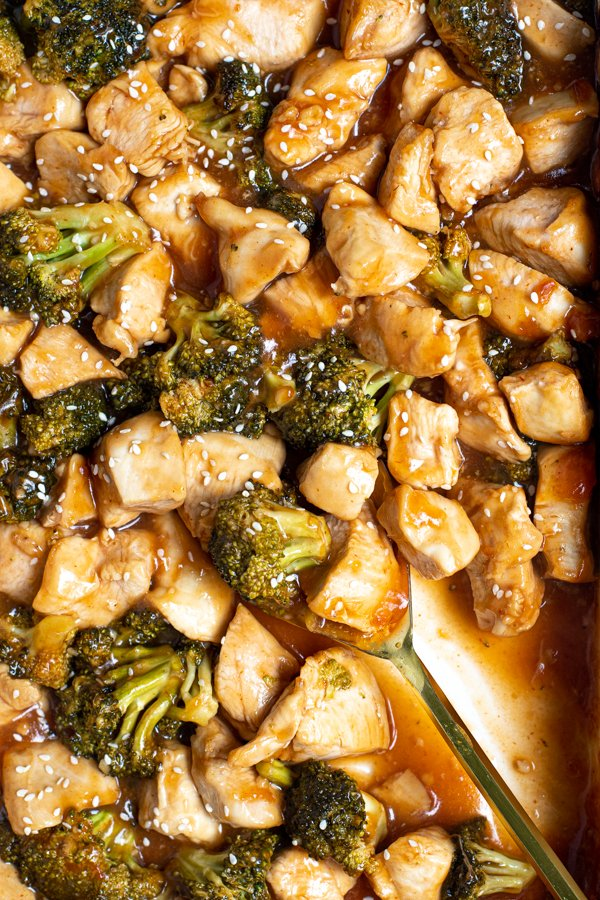 a large gold serving spoon in a baking dish filled with saucy general tso chicken