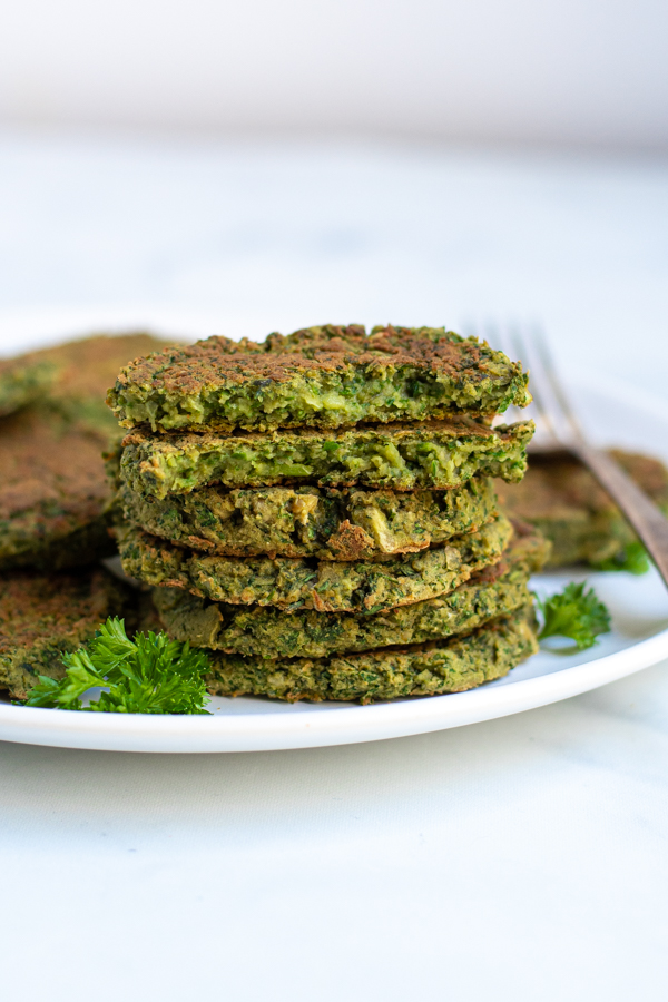 a stack of baked falafel on a white plate with the top patty broken open to reveal inside