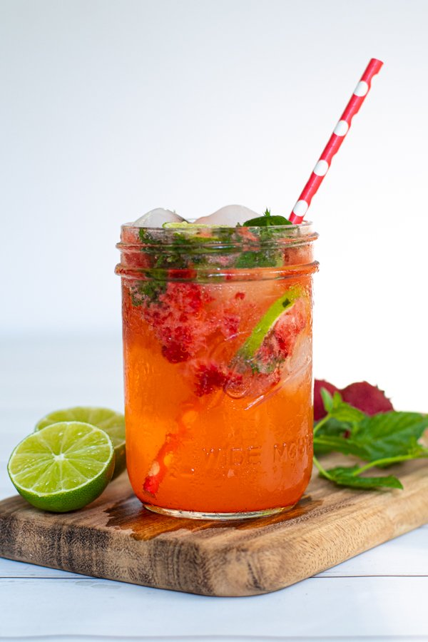 a mason jar glass full of pink strawberry mojito mocktail with fresh mint and lime slices as garnish with a red paper straw for drinking