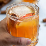 Pinterest Pin with text overlay Apple Cider Bourbon Cocktail, image of hand holding a whiskey glass full of bourbon cider garnished with cinnamon stick and apple.