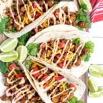 Pinterest Pin with text overlay Quick and Easy Chicken Tacos showing a platter of chicken tacos in flour tortillas next to a red towel and slices of limes.