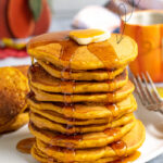 Pinterest Pin with Text overlay Pumpkin Spice Pancakes with image of a stack of pancakes on a white plate topped with a rad of butter and maple syrup dripping down the sides of the pancakes.