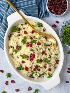 Rice Pilaf with Cranberries in a white oval serving dish with a matte gold serving spoon, garnished with dried cranberries and fresh parsley.