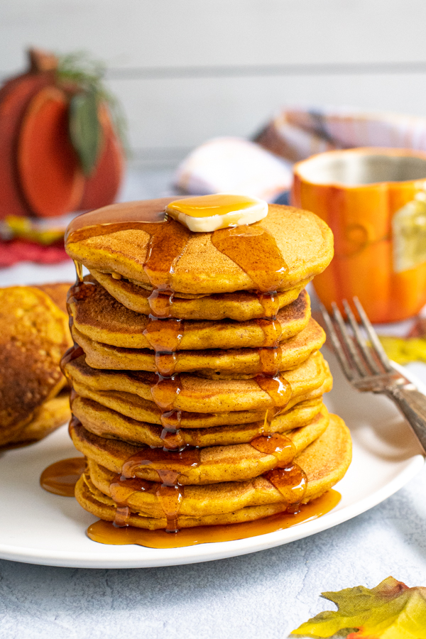 Stack of fluffy looking pumpkin pancakes on a white plate topped with a pad of butter and maple syrup running down the sides and pooling on the plate.