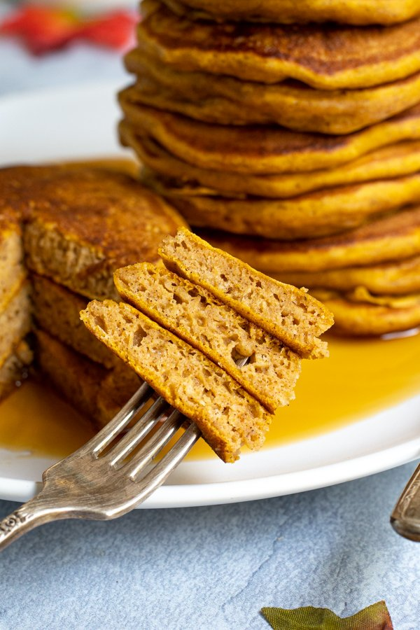 A bite full of pumpkin pancake on a fork resting on the side of a white plate next to a big pool of maple syrup.
