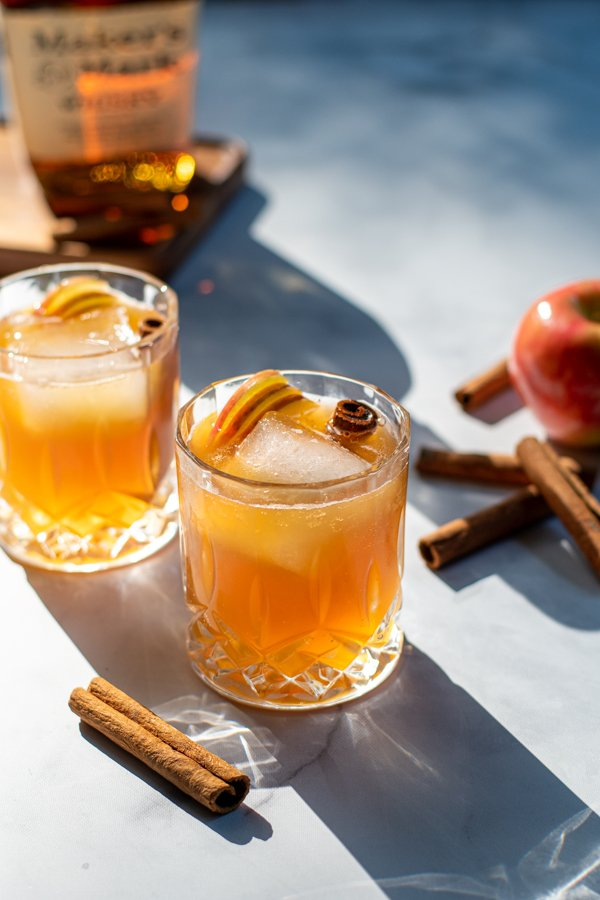 Hard sun light hitting two nice whiskey glasses full of apple cider bourbon cocktail garnished with cinnamon sticks and apple slices.