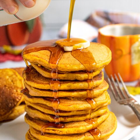 A tall stack of pumpkin pancakes on a white plate, a hand is pouring maple syrup from a jug over the top of the pancakes leaving the syrup to drip down the sides of the stack.