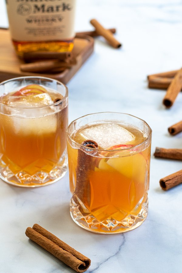 two whiskey glasses full of bourbon apple cider on a table next to cinnamon sticks and a bottle of bourbon.
