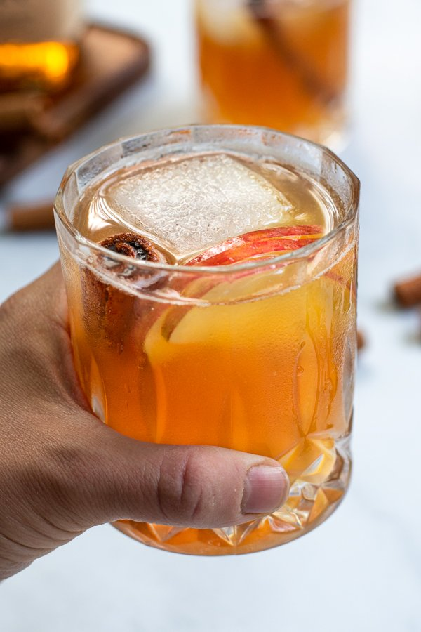 A hand holding a fancy whiskey glass full of Bourbon Apple Cider with a large ice cube, cinnamon stick, and apple slices.