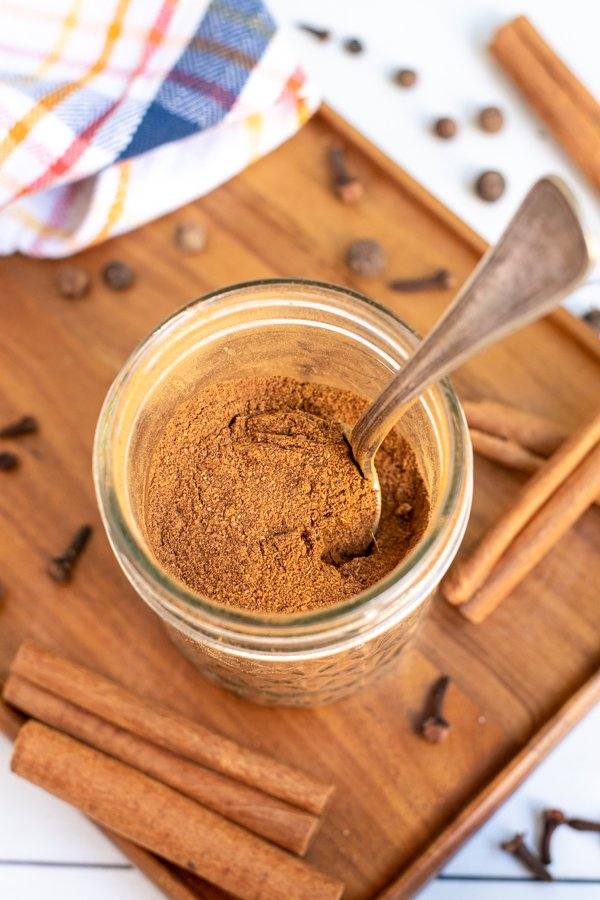 A small jar on a wooden board, in the jar is a spoon and a brown pumpkin pie spice blend.