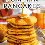 Pinterest Pin with Text overlay Homemade Pumpkin Pancakes showing a tall stack of pancakes on a white plate with maple syrup being poured on the top and dripping down the sides of the pancake.
