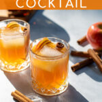 Pinterest Pin with text overlay Apple Cider Bourbon Cocktail, image of whiskey glass full of bourbon cider garnished with cinnamon sticks and apple slices.