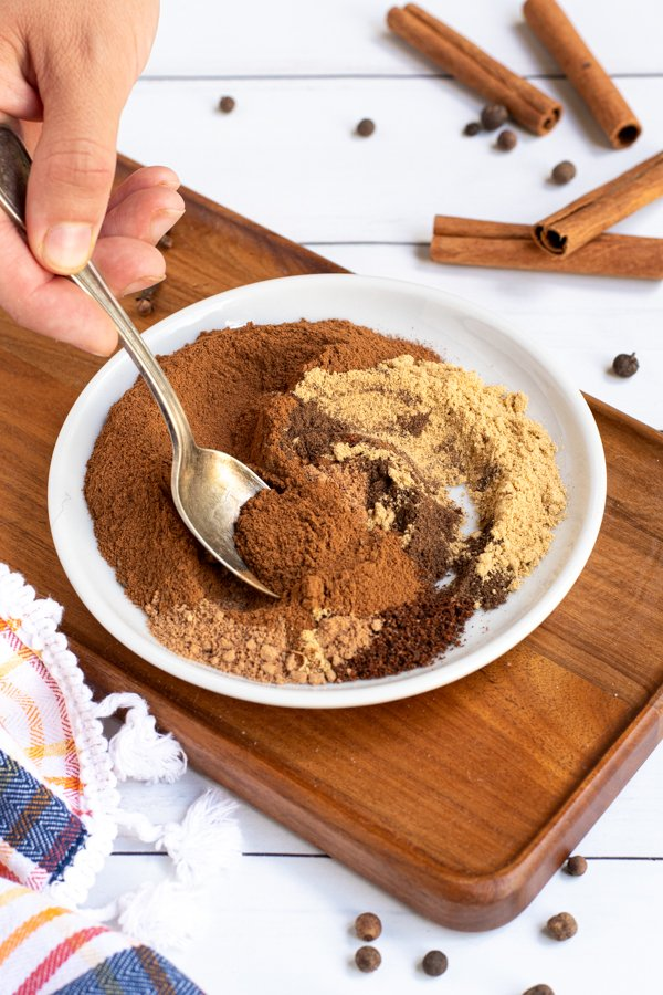 On a small white plate a spoon is stirring together the piles of different spices used to make pumpkin pie spice mix.