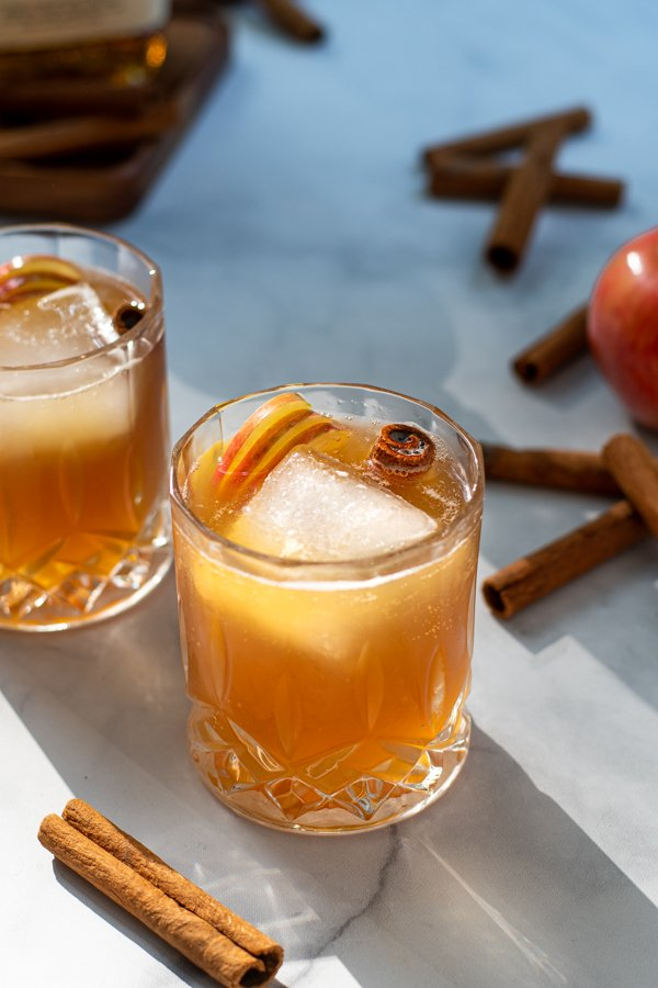 Two whiskey glasses full of apple cider bourbon garnished with a cinnamon stick and apple slices.