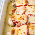 Pinterest Pin with text overlay 'Pesto Chicken Bake' showing a white baking dish with cooked chicken covered in pesto, tomatoes, and melted mozzarella.