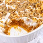 Pinterest Pin with Text: Sweet Potato Casserole with Marshmallow & Oat Streusel, showing a casserole dish with a scoop of sweet potatoes taken out.