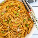 Pinterest Pin with text, One-Pot Teriyaki Noodles. Image of white bowl full of saucy noodles sitting next to a pair of chopsticks.