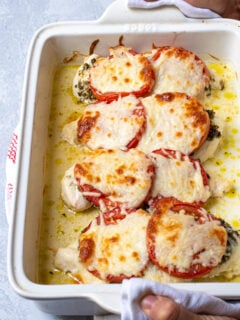 Hands holding a white baking dish containing pesto chicken bake, showing off melted mozzarella cheese on top.