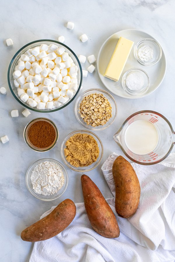 Ingredients for Sweet Potato Casserole with Marshmallows and Oat Streusel laid out on a table with a kitchen towel.