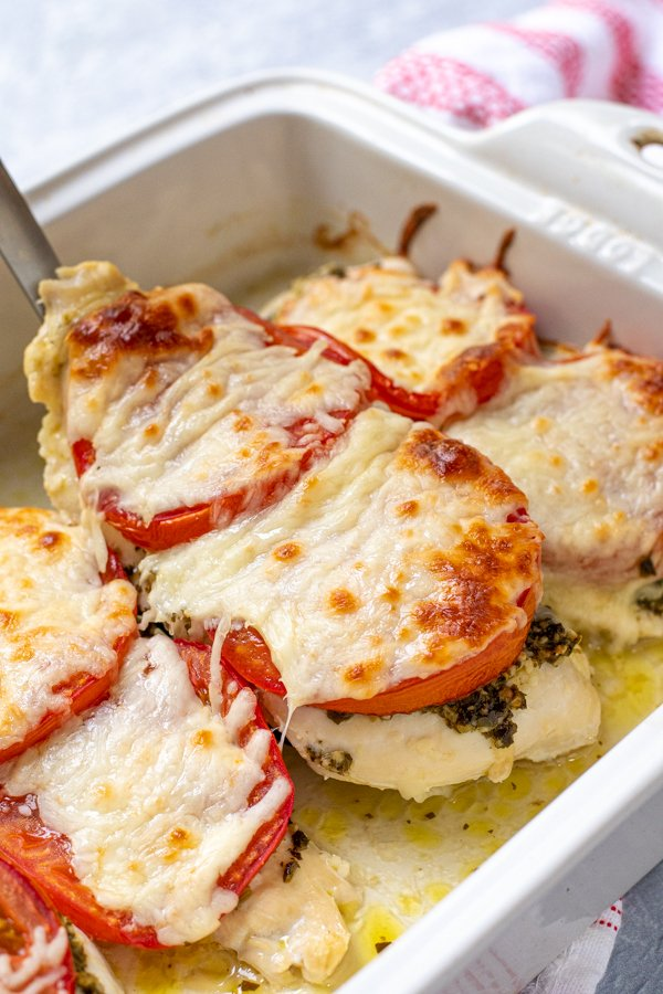 Spatula lifting a baked pesto chicken cutlet out of a dish, covered in melted mozzarella cheese.