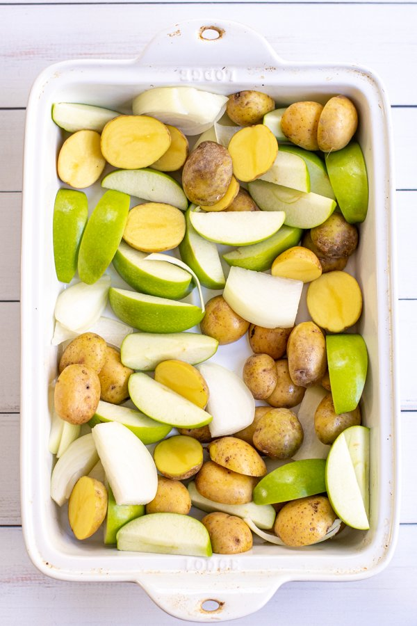 A large white baking dish holding halved baby potatoes and sliced onions and apples.