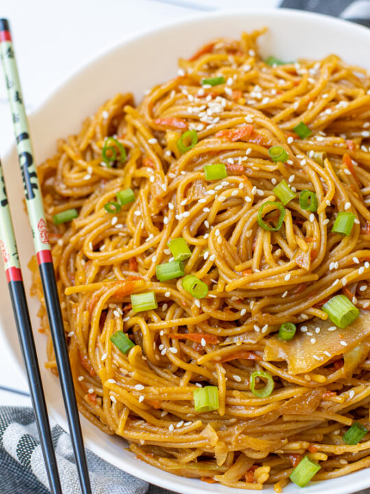 Freshly made Teriyaki Noodle Recipe in a large white bowl garnished with green onions and sitting next to a pair of chopsticks.