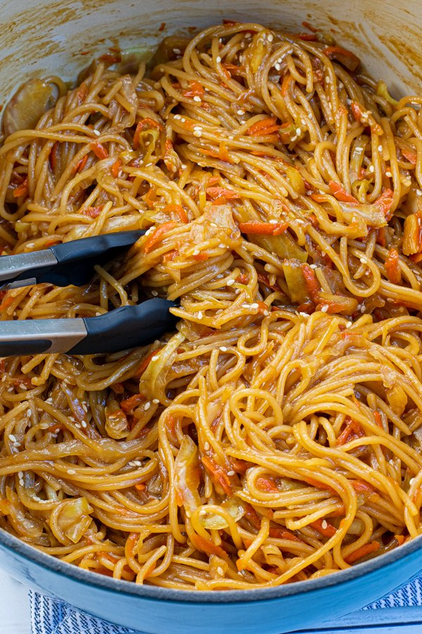 Close up of freshly cooked noodles in a large pot with a pair of tongs.