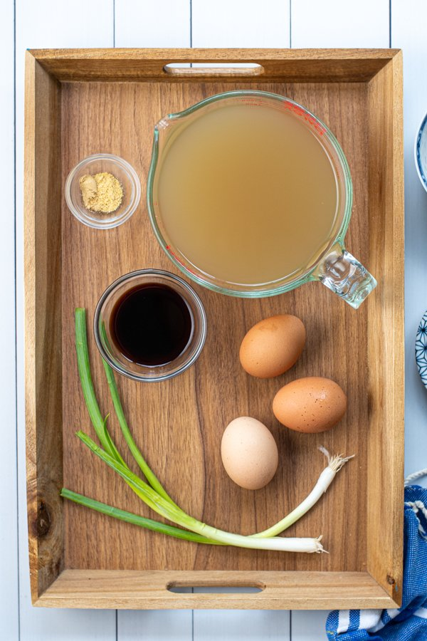The simple ingredients needed to make egg drop soup sitting on a wooden tray.