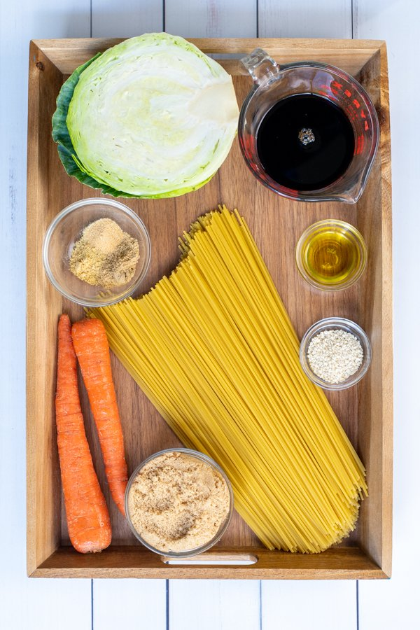 All of the ingredients needed for teriyaki noodles recipe laid out on a wooden tray.