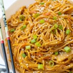 Pinterest Pin with text, One-Pot Teriyaki Noodles. Image of a while bowl of saucy noodles with chopsticks and topped with sesame seeds and green onions.
