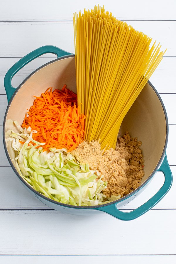 In a large teal dutch oven is uncooked ingredients for teriyaki noodles including spaghetti, cabbage, carrots, and spices.