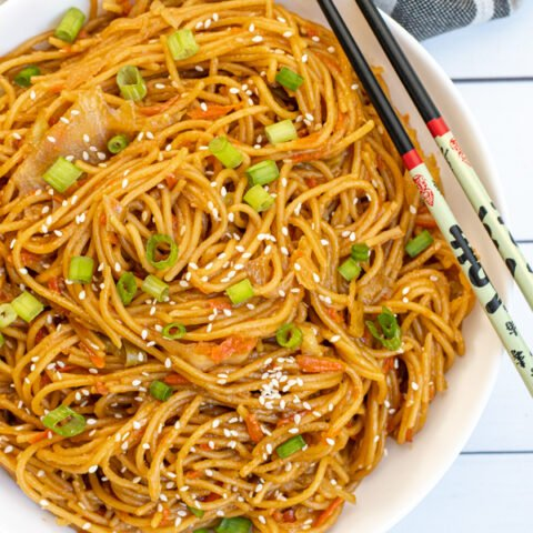 Overhead view of a bowl of noodles with carrots, cabbage, and sesame seeds with a pair of chopsticks.
