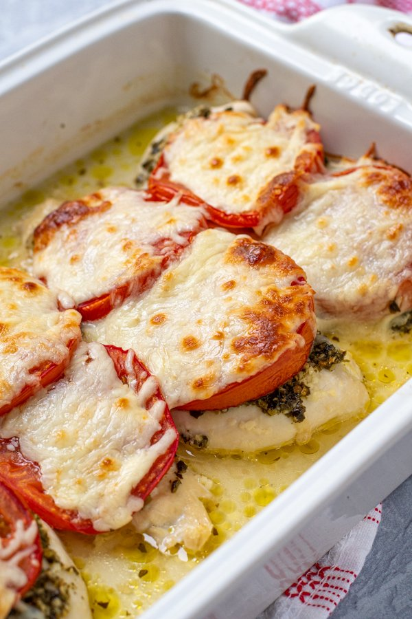 close up of a chicken cutlet baked in a dish with pesto, tomatoes, and mozzarella cheese.